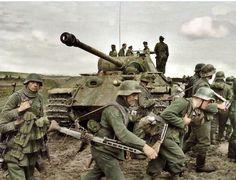 """Panzergrenadiers desde el 131st. La División de Infantería (Wehrmacht) caminaba por los campos de barro revueltos para avanzar cerca del campo de batalla. El Panzer V (Panther) que están pasando es un tanque de comando perteneciente a la 5 ª División Panzer SS """"Wiking"""". Nota sobre la parte superior del tanque es SS"""