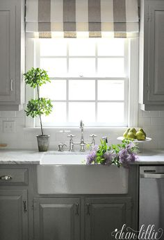 We love interest this striped faux roman shade adds to this gray and white kitchen. And the pops of green from the pears from HomeGoods add a bright touch to the kitchen. And you can't beat a farmhouse sink full of fresh cut lilacs. (sponsored)