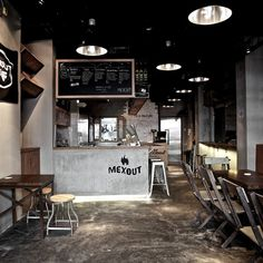 Mex Out, Far East Square, Singapore. Urban industrial setting, with lots of bare concrete brightened up by a nice logo and some educational drawing, dark characterful wood furniture topped off with big fat metal pendant lights above.