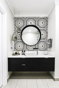 """In this Melbourne bathroom, a Moroccan inspired Schumacher wallpaper called Nasrid Palac Mosaic in Mica from Grant Dorman Interior Products tricks the eye into thinking it's resting on tiles. """"It's a hand-painted paper in black, white, gold and silver that ties the room together beautifully,"""" says interior designer Teresa Kleeman of Embracing Space. The mirror is a masterful match for it. *Photograph by Tahnee Jade.*"""