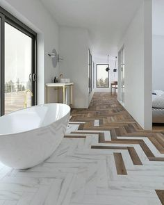 Modern, neutral bathroom with freestanding bath and herringbone floor, herringbone wood floor and ma