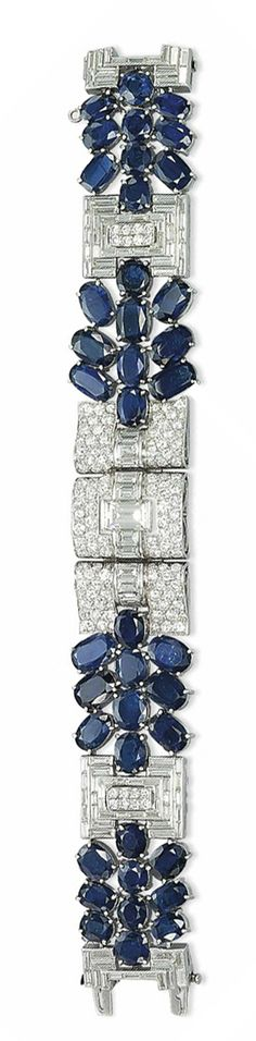 AN ART DECO SAPPHIRE AND DIAMOND BRACELET   The pavé-set diamond three-panel centerpiece applied with a line of rectangular-cut diamonds, to the oval-shaped sapphire clusters linked by baguette-cut diamond tiered rectangular-shaped spacers, centering upon pavé-set diamond motifs, mounted in platinum, 1930s, 16.8 cm