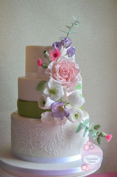 #Weddingcake decorated with blush sugar #rose, #ranunculus, #lisianthus, #sweetpeas, #eucalyptus foliage and....... #gumnuts! (a nod to the bride's Aussie roots). #Lace brush embroidery inspired by bride's wedding dress.  Flavours ~ rich dark Belgian chocolate top and bottom tiers and Madagascan vanilla in the middle.