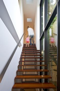Minimalist-staircase-design-in-narrow-space-with-floating-wooden-steps-and-mounting-handrail-along-with-vertical-windows-and-ceiling-lamps-decoration.jpg