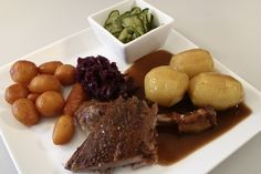 Danish national Christmas dish. Duck with apples and prunes, with both white and caramelized potatoes, sour-sweet red cabbage and pickled large cucumbers