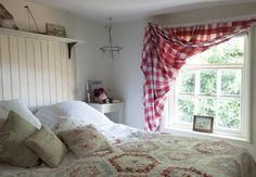 Cottage bedroom with patchwork quilt and gingham curtain at window