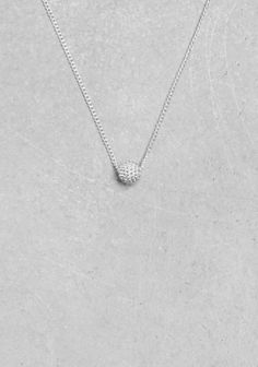 An ultra-delicate chain necklace topped with a tiny embossed ball pendant.