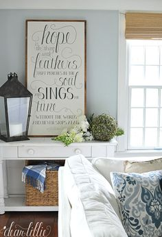 "Touches of blue like the throw and pillow both from HomeGoods add a summery touch to this corner of this blue and white family room and go nicely with the Emily Dickinson, ""Hope is the thing with feathers..."" sign. (sponsored pin)"