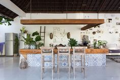 The sunken kitchen/bar area is framed with hanging plants and big pool.