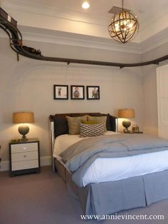 Street of Dreams Arizona - Via Annie Vincent Interiors - Gorgeous boy's bedroom with armillary style chandelier hung from tray ceiling with overhead train track below against a backdrop of ticking patterned wallpaper accented with framed kid's photography over a Restoration Hardware Kid's Aviator Headboard dressed with gray and white bed linen topped with a geometric taupe pillow.