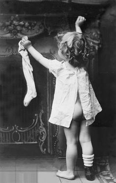 vintage black & white photography | little girl pinning her sock to the mantle piece or fire place | christmas time | santa stocking | bare bottom | sweet