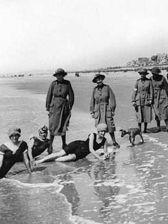 Women's Auxiliary Army Corps members, France, during World War I. This photograph, which is attributed to Tom Aitken, shows a group of women from the Women's Army Auxiliary Corps (WAAC) on the beach beside a town in France. Five of the women are wearing their uniform overcoats and hats. The other three are in swimsuits. The WAAC was established in January 1917 to replace men in some non-combatant roles such as clerks, telephonists or cooks.