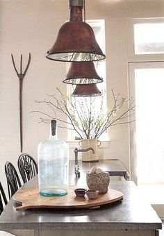 Country house style: Copper lighting, large round wooden bread board, crock pot filled with twigs...love the pitchfork on the wall.