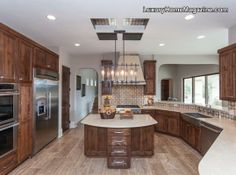 Stunning wood kitchen with center island. The lighting centerpiece is absolutely beautiful and the stainless steel appliances add a sleek finish! -- Luxury interior design, home decor, and decorating ideas --