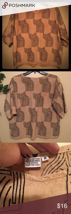 Tribal looking cat shirt. One of a kind I would never let this go but unfortunately my frame is to small with narrow shoulders so can't get it to fit me the way it should 😖. Same pattern all over, it's a tan color with black unique cat designs all over also. Short sleeves go down to your elbow. There is no name brand--I travel out of the country & buy things from all over. Just like brand new❣️😻 Tops