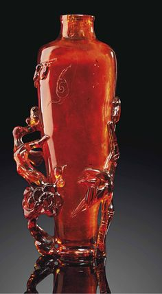 A SMALL CARVED AMBER BOTTLE VASE  19TH/20TH CENTURY  The vase is of tapering form with a short domed foot and a waisted neck. The sides are carved and pierced with two birds above bamboo and prunus branches. The amber is of an attractive and rich dark orange tone.