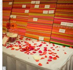At the reception, tables were covered in white linens and sprinkled with rose petals and small tea light candles, while the escort card display was wrapped with orange and pink ribbons.