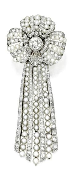 A Belle Epoque Seed Pearl and Diamond Clip-Brooch, France, Circa 1910. Of ribbon design with an articulated tassel, centered on an old European-cut diamond, millegrain-set with single-cut diamonds and seed pearls, with French assay marks.