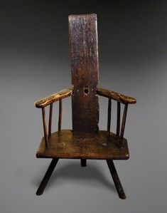ANTIQUE STICK CHAIR 18th century Welsh stick chair with a single plank back (possibly later) and one-piece shaped armrest above a low solid seat, raised on three legs Antique Chair Welsh Chairs