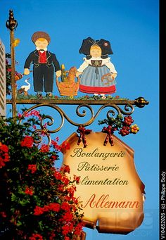 Traditional iron sign, for an Alsatian bread shop, showing a couple in traditional clothing Alsace, Blade Sign, Storefront Signs, French Signs, Shop Signage, Pub Signs, Shop Fronts, Business Signs, Store Signs