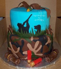 "Duck Hunters Groom Cake - 8"" & 10"" cakes iced in fondant with hand made fondant duck, shells, duck calls, & cat tails. All of the camo pieces, grass, & dog/hunter were hand cut out of fondant. TFL!"