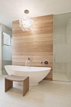 Badezimmer mit freistehender Badewanne, Vorwand Dusche mit Fliesen in Holzoptik.