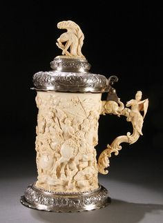 AN EXCEPTIONAL GERMAN CARVED IVORY AND SILVER MOUNTED TANKARD WITH ROMAN BATTLE SCENE, HANAU, CIRCA 1880-1890. The cylindrical form masterfully carved in high relief with a chaotic Roman battle scene of mounted horseman battling Turks below a silver domical cover with embossed and chased horsemen and surmounted with a well carved Roman feathered helmet finial. The ivory handle emanating from an elephant head mount, well carved with an amusing seated soldier displaying sword and shield.