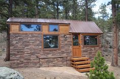 This is a tiny stone cottage — on wheels! From the outside, you'll notice beautiful stone siding all around the base of the house and a gable-style metal roof with dormers for the loft.…