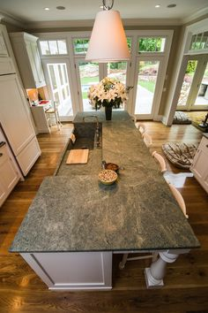 Costa esmeralda granite warms up this kitchens island and breakfast bar. The green tones highlight the white cabinets perfectly #connecticutstone