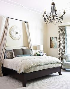 A bright and simple bedroom decorated in neutral tones, with a wonderful, cozy-looking bed accented by a draped half-tester canopy  (via For the Home)