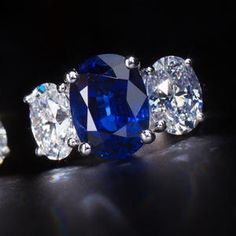 A sapphire and diamond ring set with an oval-cut sapphire, weighing 6.60 carats, flanked by oval-cut diamonds, weighing 2.02 and 2.03 carats; mounted in eighteen karat white gold.