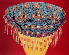 A Qing Dynasty era double-happiness wedding headdress covered with kingfisher feather, inlaid with pearls, jade and red coral, from the Forbidden City Palace Museum collection.