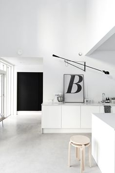 Full of stunning and graphic contrast, Paolo Rizzatto's 265 lamp introduces strong lines to complement this black and white kitchen.