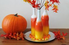 What better thing to re-purpose after a weekend of Halloween than all those empty wine, liquor, and beer bottles? Here's a quick and easy way to create an ombre wine bottle centerpiece – all you need is a few cans of spray paint!    We went for a candy corn motif but any color combination would do the trick!