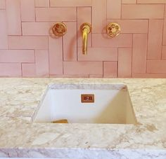 Perfect pink cement herringbone tiles with polished brass taps, wall hung with wheel details; all by Bert and May London