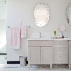 Behr Silver Drop Love It or List It - Stunning bathroom features etched, oval mirrors over gray double washstand topped with Caesarstone Organic White countertops and carved backsplash atop mosaic marble floor accented with black border tiles.