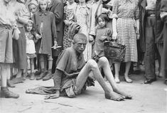 Famine stricken man sitting on the sidewalk in the Warsaw ghetto. The presence of the photographer has attracted onlookers, August 1941. This was not an uncommon sight, many people died of hunger and disease in the Warsaw ghetto. Many who survived the hardships endured there were sent off to concentration camps.