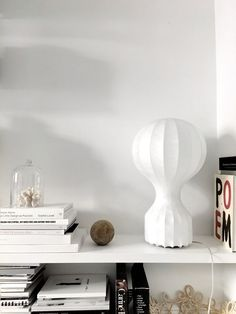 The Gatto table lamp fits in seamlessly with this white minimalist interior with stacks of books and unique art.