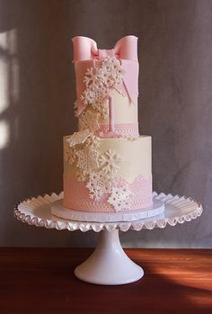 Pretty pink lace and delicate gumpaste snowflakes accent this cute 1st birthday cake.