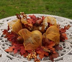Details designed to WOW! This Eye catching centerpiece showcases unique loveliness at every turn. 41 inches around and 14 inches diameter, this unique mesh centerpiece is elegant while interesting. It was made with a combination of life like artificial Fall leaves and a very Autumny shade of mesh fabric. While remakes are possible, each will be unique. Please inquire on quantity requests. Outdoor safe. NOTE Do not use flame candles with this centerpiece Perfect as a standalone decoration…