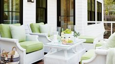 Nostalgic white wicker furniture and a striped cabana awning create a striking contrast to the modern black windows on the second-floor porch. The cushions on the deep-seating chairs are 3 inches thick, making the open-air living room as comfy for curling White Wicker Patio Furniture, White Wicker Chair, Porch Furniture, Wicker Chairs, Outdoor Furniture Sets, Furniture Layout, Cheap Furniture, Furniture Plans, Kids Furniture
