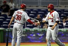 Yadler Molina celebrates scoring a run with teammate Pete Kozma during the first inning of a game against the Marlins.  Cards won the game 13-7.  6-15-13