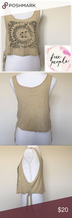 🎉HOST PICK🎉 We The Free Graphic Beige Tank Tee EUC Cropped semi distressed top features graphic design as shown on pic. Tie backs on each side of tee. Sz S/P. Great layering piece even as a bikini cover up. Free People Tops Crop Tops