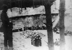 Members of Einsatzgruppen A, the Ordnungspolizei and the Wehrmacht, as well as Lithuanian collaborators, prepare to begin mass executions of Lithuanian Jews held in a quarry pit.