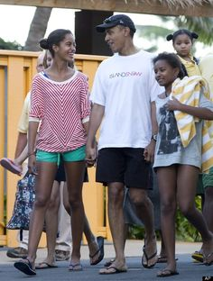 President Barack Obama holding hands with his daughters Malia, left, and Sasha, right, leave Sea Life Park, a marine wildlife park, with family friends, Tuesday, Dec. 27, 2011, in Waimanalo, Hawaii. (AP Photo/Carolyn Kaster)