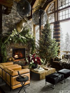 In a Yellowstone ski house decorated with a Christmas tree, holiday flowers and garlands, the living area's sectional sofa and cable-knit rug are by Ralph Lauren Home, the barnwood cocktail table is a custom design, the black side table is by Arteriors, and the pair of black ottomans were found at Costco; the pendant lights are by Moooi, and the curtains are of a Sandra Jordan alpaca.