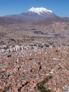 via www.mountainadventures.com  Illimani (21,184ft) looms over the crowded city of La Paz, Bolivia