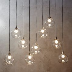 """$429.00  Shop firefly II pendant light.   Industrial modern chandelier by Mark Daniel suspends nine glass globes from nickel-finished iron canopy.  Pendants stagger in length on black cords 19"""" to 52"""".  Great look with filament bulbs or our 25W candelabra bulb."""