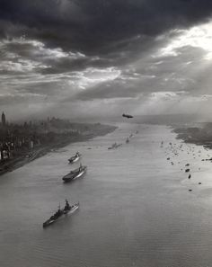 Tugboats and U.S. Navy warships pictured in the Hudson River with the New York City skyline in the background for the Navy Day celebrations on 27 October 1945. Visible in the foreground are the anchored warships USS Augusta (CA-31), USS Midway (CVB-41), USS Enterprise (CV-6), USS Missouri (BB-63), USS New York (BB-34), USS Helena (CA-75), and USS Macon (CA-132)