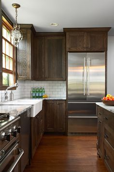 Gorgeous kitchen with dark stained shaker cabinets adorned with oil-rubbed bronze cabinet pulls alongside Arabesque White Granite countertops and white subway tile backsplash. Dark Stained Cabinets, Dark Wood Cabinets, Kitchen Ideas With Brown Cabinets, Dark Cabinets White Backsplash, Kitchens With Dark Cabinets, Dark Brown Kitchen Cabinets, Walnut Cabinets, Farmhouse Kitchen Cabinets, Shaker Cabinets